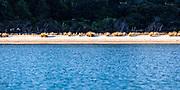 Te Matuku Bay, McLeods Bay, Waiheke Island. Water, white beach, tussock grass, and native bush.