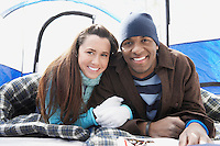 Young couple lying in sleeping bags in tent portrait.