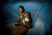 Agatha Mutunda and her youngest child Cretus, inside her home in Katombora village, 60kms outside the Zambian town of Livingstone. The village has been one of many that have benefitted from the distribution of mosquito nets from international public health companies. Since the introduction of mosquito nets in this area there has been a rapid decline in the number of people suffering from malaria.26 April 2008