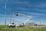 "Western Farmers Electric Coop lineman work to install a high voltage electrical switch at a substation near Perry, OK.  They are working on the line that carries 67,000 volts per phase, using a technique they call ""bare handed"" ie working with live voltage."