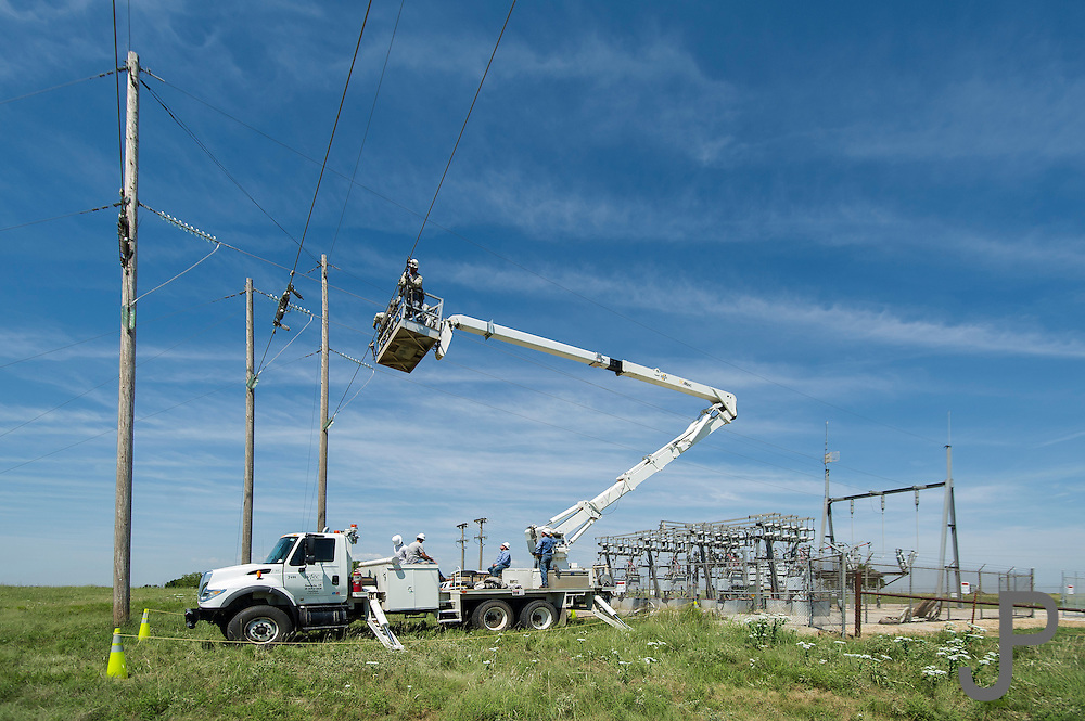 """Western Farmers Electric Coop lineman work to install a high voltage electrical switch at a substation near Perry, OK.  They are working on the line that carries 67,000 volts per phase, using a technique they call """"bare handed"""" ie working with live voltage."""