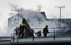 © licensed to London News Pictures. London, UK 04/02/12. Firefighters on the roof, Over 100 firefighters are working to bring a fire on Grafton Street in Mayfair, London under control. The fire which started early this morning is in a terrace building that sold for 13million GBP in 2007. Photo credit: Tolga Akmen/LNP