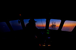 Pilot boat captain's of a jack up drilling rig with a colorful sunset.