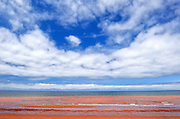 Red sandy beach and clouds. Northumberland Strait
