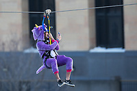 Minneapolis, MN - January 26, 2017: Bold North Zip Line rider Brett Evenson, wearing a purple unicorn costume,  zooms down the line and over the Mississippi River as part of the SuperBowl LII events taking place in Minneapolis.