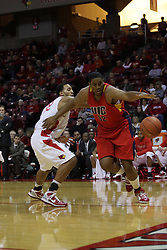 11 December 2010: Darrin Williams almost looses control of the ball going around Jackie Carmichael on the baseline during an NCAA basketball game between the Illinois - Chicago Flames (UIC) and the Illinois State Redbirds (ISU) at Redbird Arena in Normal Illinois.