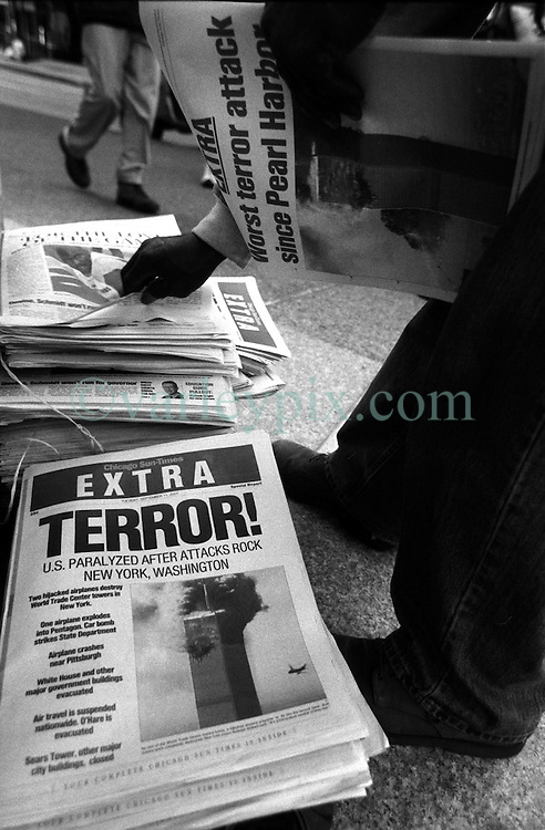 11 Sept 01. Sears Tower, Chicago, Illinois.<br /> Passers by pick up 'Extra Terror' from the Chicago Sun-Times in a special early edition of the paper on the morning of 9-11 under the Sears Tower, the USA's tallest skyscraper. Sears Tower was evacuated. At this time 3 planes were still unaccounted for and it was assumed that the Sears Tower could be a potential target for radical Islamic Al Qaeda terrorists who had already flown planes into the World Trade Center, the Pentagon and crashed a 4th plane into a field in Somerset County, Pennsylvania.<br /> Photo credit©; Charlie Varley/varleypix.com.