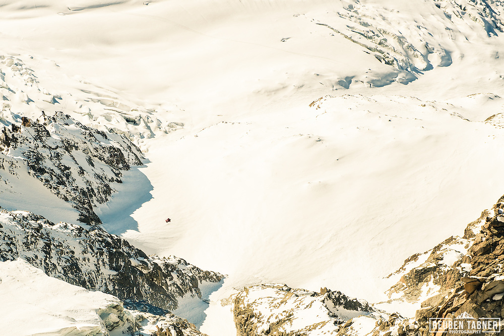 Nathan Jones a wingsuit pilot flys over a snow field on the Aiguille du Midi above Chamonix, in a wingsuit.