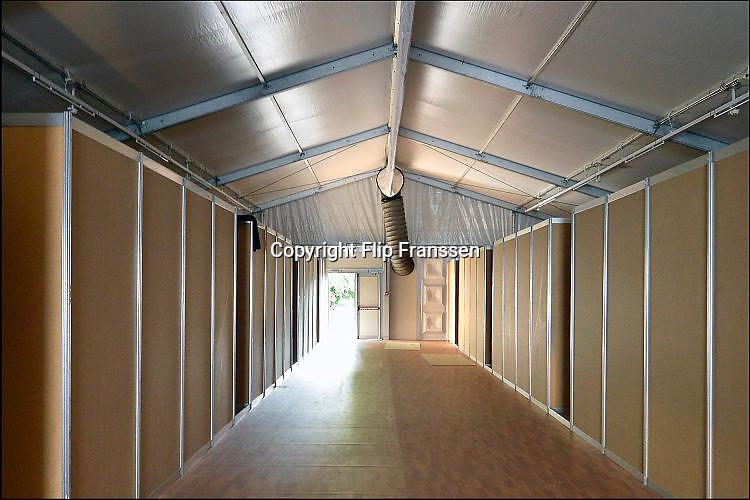 Nederland, the Netherlands, Nijmegen, 2-10-2015 Eerste vluchtelingen arriveren op kamp, tentenkamp Heumensoord, de tijdelijke noodopvang, azc, van het COA. Op de foto een tent met slaapunits, verblijven. Te zien is de grijze buis bij de deur waar de warme lucht voor de verwarming doorheen geblazen wordt om de tent van warmte te voorzien. Vandaag komen er 300, later dit weekend wordt het tot 800 aangevuld. In totaal komt er plaats voor 3000 asielzoekers. Aan het kamp wordt nog volop gewerkt aan met name de infrasrtuctuur voor elektra, afvoer en water. FOTO: FLIP FRANSSEN/HH