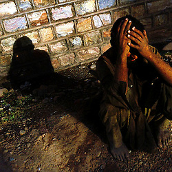 A Certain Fate - A heroin smoker, squatting on the unmarked roadside graves of former addicts, covers his face in the setting sun of Pakistan's northwest Tribal Areas. About thirty shallow graves ddicts line the alleyway..