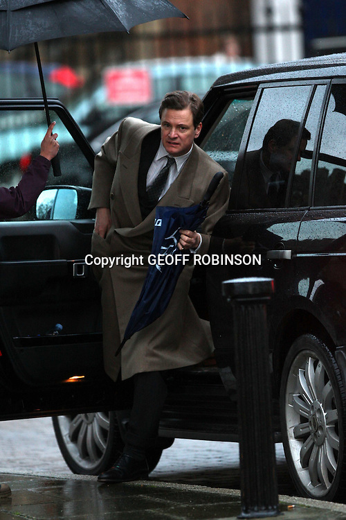 COLIN FIRTH AS GEORGE VI IN HIS NEW FILM... He is famous for getting wet but Colin Firth made sure he was protected from the rain on the set of his latest movie...The period actor sheltered under an umbrella as he stepped out for the first time as the Queen's father in the new film The King's Speech...Colin, 49, who plunges into a lake and emerges with a dripping wet shirt as Mr Darcy in Pride and Prejudice, wrapped up warm for his role as King George VI...He looked royally handsome with his hair slicked back and wearing a suit and the King's famous brown overcoat. ..It was the first day of filming at Ely Cathedral in Cambridgeshire, which is being used to portray Westminster Abbey...The movie, which is to be released next year, tells the story of the relationship between England's reluctant King, George VI, who had a nervous stammer, and the irreverent Australian speech therapist who helped him...SEE COPY CATCHLINE Colin Firth stays dry on set