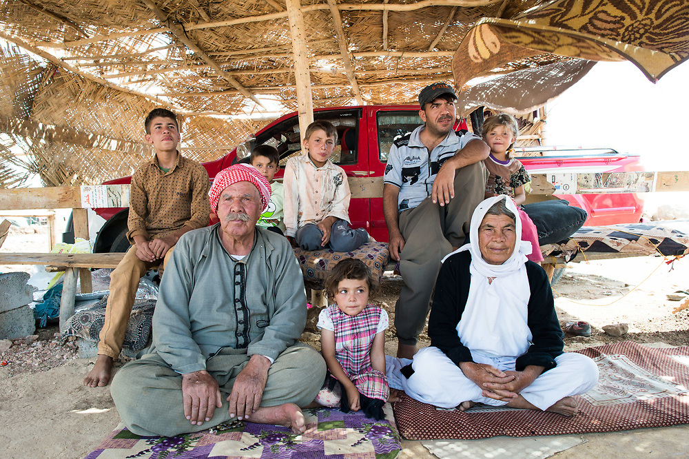 75-year-old Ali (front left) sitting with his relatives next to his provisional tent. When ISIS overran Shingal he – like many other older people – could not flee. ISIS took him to Tal Afar. He has been liberated in January 2015 and went back to Shingal. There, he wants to defend himself from ISIS whenever necessary because he no longer trust to the Kurdish peshmerga that they will protect him. Shingal (Sinjar), Iraq, August 28, 2015
