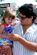 Father giving balloon art to daughter at Aquatennial  age 26 and 4.  Minneapolis Minnesota USA
