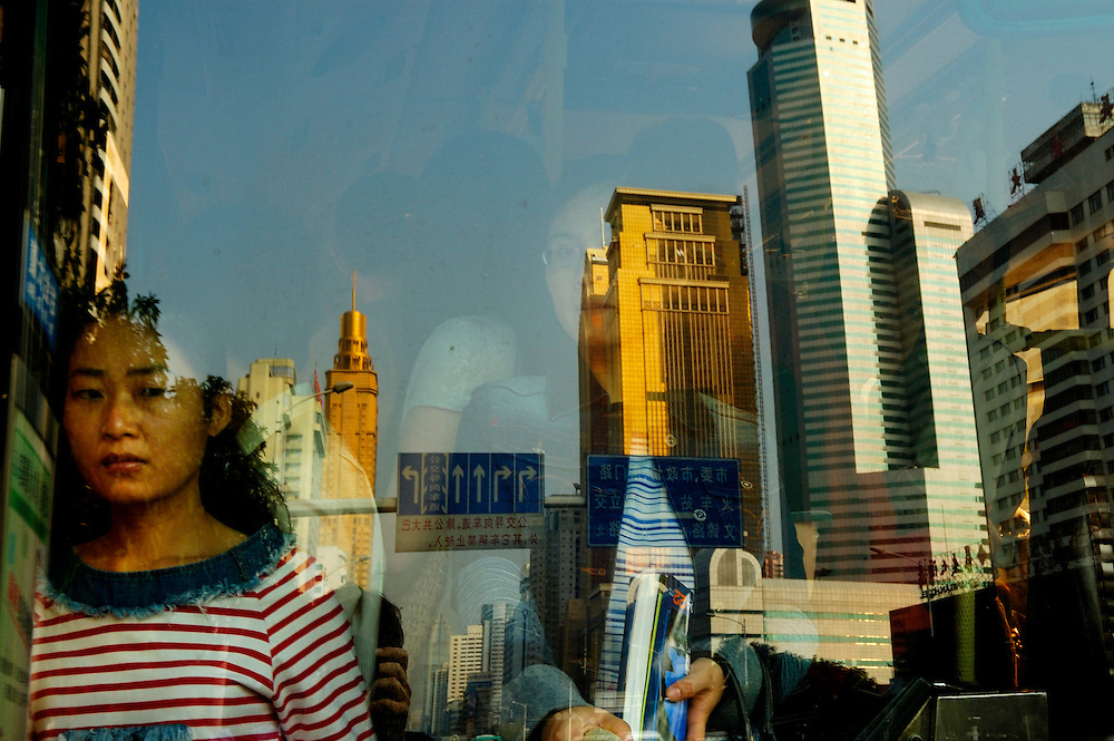 Commuters on their way to work on a crowded city bus with downtown city skyscrapers reflected in the window...From China [sur]real © Mark Henley....