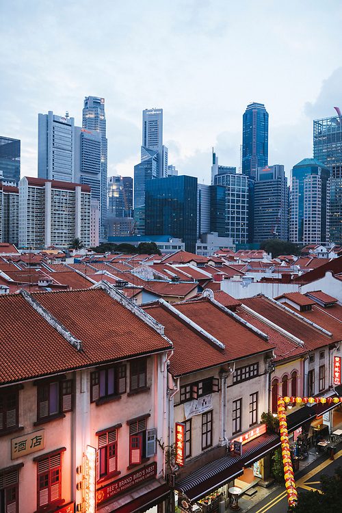 Old shophouses of Chinatown and the modern skyscrapers of Singapore at dusk.