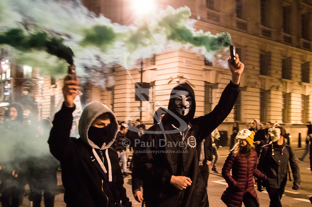 London, November 5th 2016. Anti-capitalists and anarchists participate in the Million Mask March, an annual event that happens on November 5th each year in cities across the world, as part of a protest against the establishment. Many of the protesters wear Guy Fawkes masks, often associated with the internet activism group Anonymous. PICTURED: Protester carry smoke bombs as the march along Whitehall.