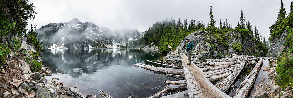 Chair Peak (6238 feet) rises through fog and reflects in calm waters at the outlet of Snow Lake (elevation 4400 feet) in Alpine Lakes Wilderness Area, Mt. Baker-Snoqualmie National Forest Trail #1013, in the Cascade Range of Washington, USA. Take Interstate 90 Exit #52 westbound or Exit #53 eastbound and follow signs to Alpental Road ski area parking lot and trailhead. To avoid crowds at this popular trail, start early and avoid sunny weekends. The trail down from the saddle viewpoint to Snow Lake is often snow covered through July 4. This image was stitched from 14 overlapping photos.