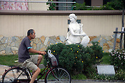 Asian man peddling past a white western classic style female sculpture