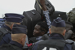 October 24, 2016 - Calais, Nord-Pas-de-Calais-Picardie, France - A refugee tries to get his suitcase from the ones hold above the queue. A minor scuffles with some pushing and shoving broke out between refugees queueing to get into the Reception and Orientation Centre at the Jungle and police officers. (Credit Image: © Michael Debets/Pacific Press via ZUMA Wire)