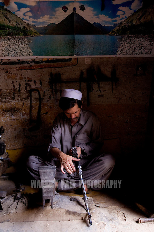 DARA ADAM KHEL, PAKISTAN - MAY 29: A gunsmith crafts a replica of an AK-47 in the tribal village of Darra Adam Khel, near the Afghan border, May 29, 2006. Darra came under the control of the Taliban in late 2006, who have since imposed strict curfews and laws on the local tribal population. In the arms trade for more than a century, the Pashtuns of Darra were trained to make ordinance by the British to regularly supply their troops in neighboring Afghanistan. Since then craftsmen have passed down their techniques from father-to-son. Their weapons have been used in conflicts from Bosnia to Kashmir due to their cheap cost, and reliable craftsmanship. (Photo by Warrick Page)