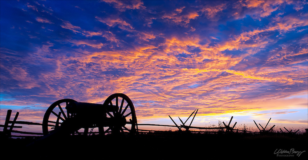 History Silhouetted - Civil War cannon and split rail fence at sunrise, Gettysburg National Park.