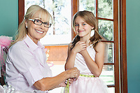 Portrait of grandmother measuring granddaughter's waist with tape