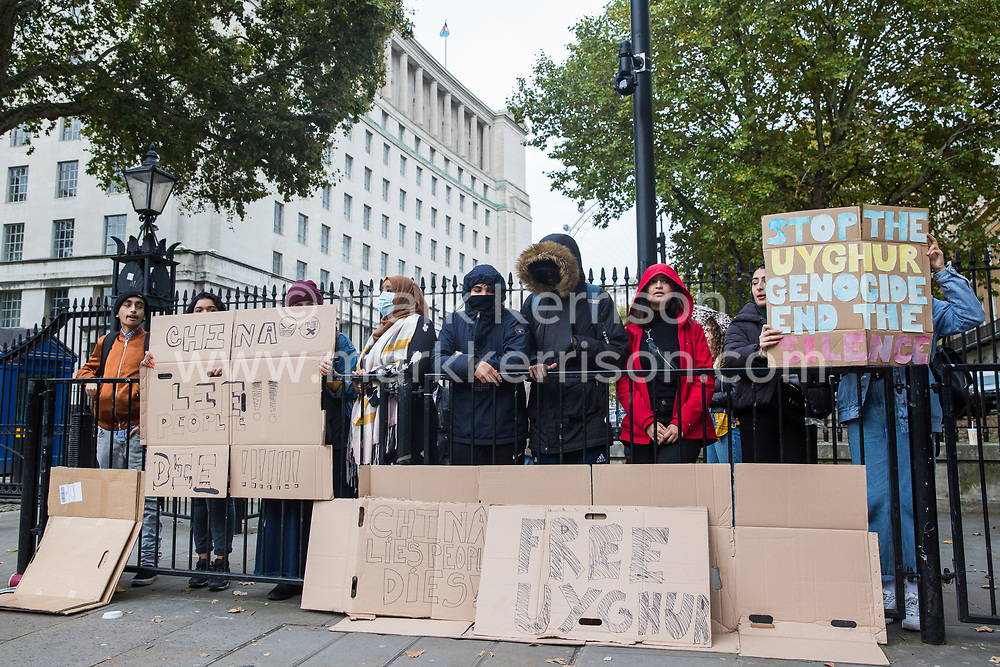London, UK. 23 October, 2019. A small group of demonstrators stands opposite Downing Street holding signs calling for an end to human rights abuses against the Uighur minority in China.