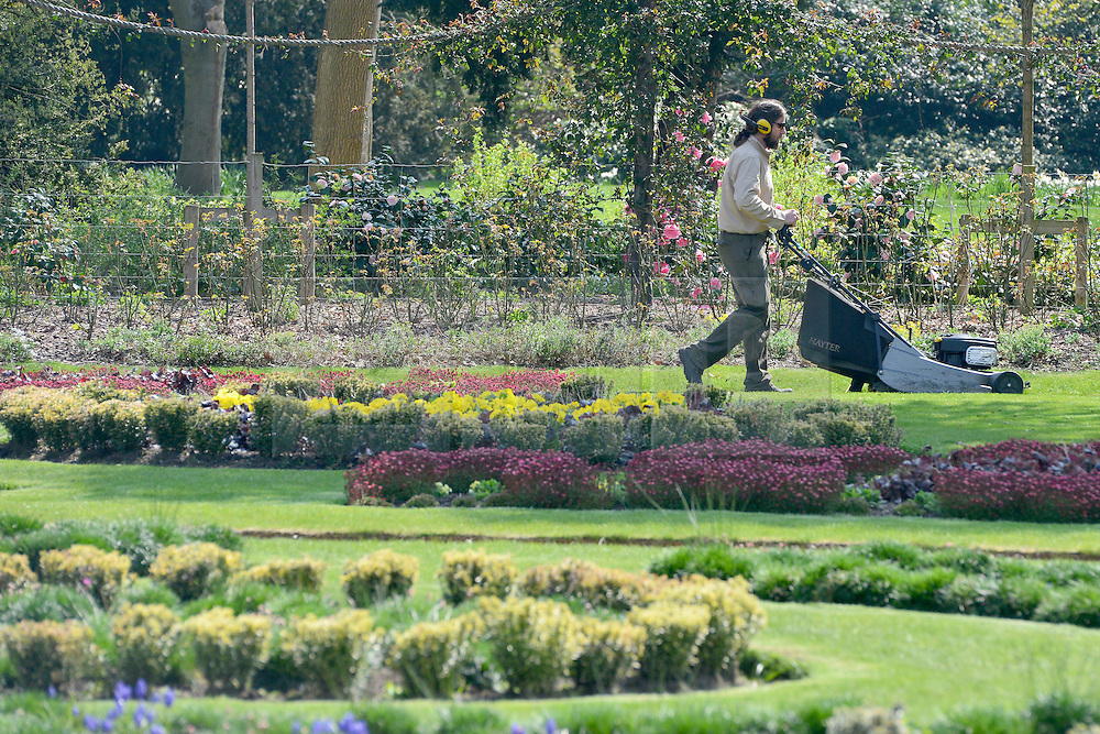 © Licensed to London News Pictures. 25/04/2013. Chiswick, UK A man mows a lawn in the ornamental gardens. People enjoy the sunshine in the grounds of Chiswick House in West London today 25th April 2013. Photo credit : Stephen Simpson/LNP