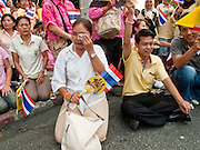 05 MAY 2010 - BANGKOK, THAILAND: A woman weeps after seeing Thai King Bhumibol Adulyade pass her and the crowd during Coronation Day, Wednesday, May 5. Wednesday was Coronation Day in Thailand, marking the 60th anniversary of the coronation of Thai King Bhumibol Adulyade, also known as Rama IX. He is the world's longest serving current head of state and the longest reigning monarch in Thai history. He has reigned since June 9, 1946 and his coronation was on May 5, 1950, after he finished his studies. The King is revered by the Thai people. Thousands lined the streets around the Grand Palace hoping to catch a glimpse of the King as his motorcade pulled into the palace. The King has been hospitalized since September 2009, making only infrequent trips out of the hospital for official functions, like today's ceremonies.   PHOTO BY JACK KURTZ