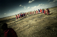 Tanzania, traditional Maasai life. All present Koriangai gather outside a Boma where festivities are held in preparation to dance as a show of strength. The routine is traditional and begins whenever someone of the Koriangai decide it is time and begin to sing and walk around slowly giving everyone time to catch up with the line.