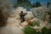 An Afghan National Army soldier fires a rocket-propelled grenade at a group of Taliban fighters.