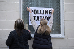 © Licensed to London News Pictures . 07/05/2015 . Doncaster , UK . A woman hangs a POLLING STATION sign outside Sutton Village Hall polling station in Ed Miliband's constituency of Doncaster North. Photo credit : Joel Goodman/LNP