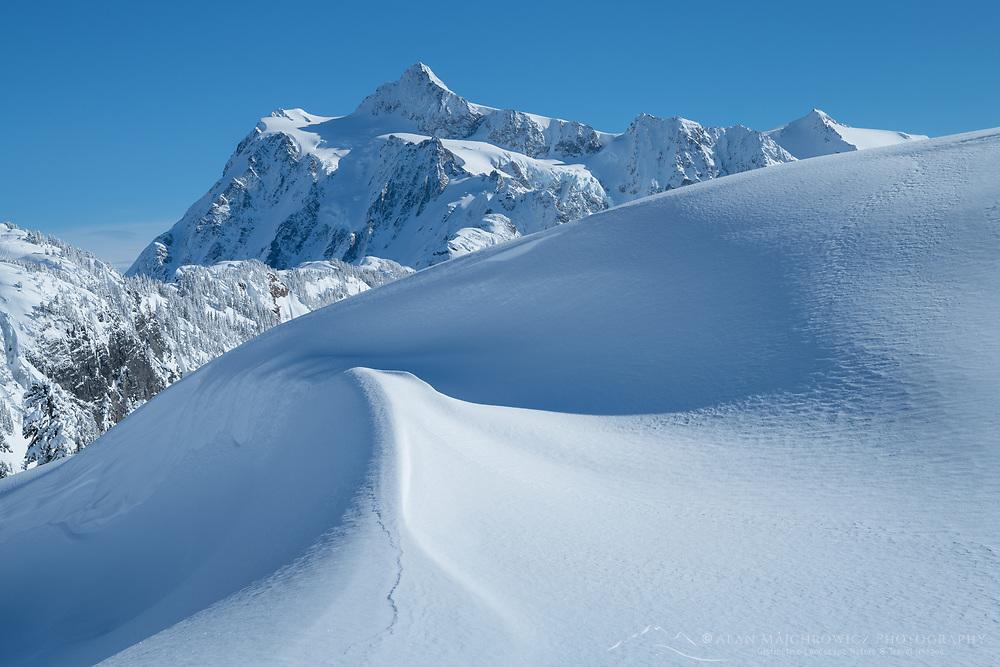 Kulshan Ridge snowdrift, Mount Shuksan is in the distance. Heather Meadows Recreation Area, North Cascades Washington