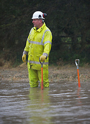 © Licensed to London News Pictures. 26/11/2012..Boulby, North Yorkshire..A worker from Redcar and Cleveland Highways department tries to clear blocked drains on the main road between Easington and Staithes following another night of heavy rain that caused disruption in parts of East Cleveland and North Yorkshire..Photo credit : Ian Forsyth/LNP
