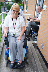 Disabled couple leaving their house down a concrete wheelchair ramp,
