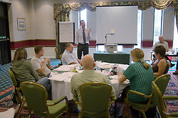 Trainer addressing a group of youth justice staff on a training day,