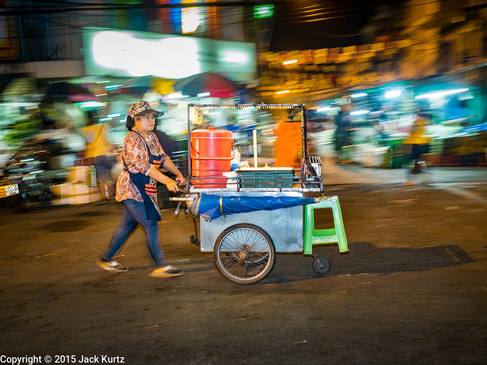 """21 DECEMBER 2015 - BANGKOK, THAILAND:  A woman pushes her food cart past the entrance to Pak Khlong Talat, also called the Flower Market. The market has been a Bangkok landmark for more than 50 years and is the largest wholesale flower market in Bangkok. A recent renovation resulted in many stalls being closed to make room for chain restaurants to attract tourists. Now Bangkok city officials are threatening to evict sidewalk vendors who line the outside of the market. Evicting the sidewalk vendors is a part of a citywide effort to """"clean up"""" Bangkok.      PHOTO BY JACK KURTZ"""