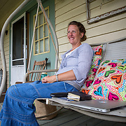 August 10, 2015, Green Bank, West Virginia: Shana Beverage, sits on her porch in Green Bank, West Virginia, where she lives with her family. Green Bank is in the heart of the United States National Radio Quiet Zone, a large area where all radio transmissions are limited to avoid emissions toward the Green Bank Telescope. There is zero cell phone coverage in the area and although WiFi is not supposed to be used, most residents have wireless internet in their homes, including the Beverages. Photo by Evelyn Hockstein