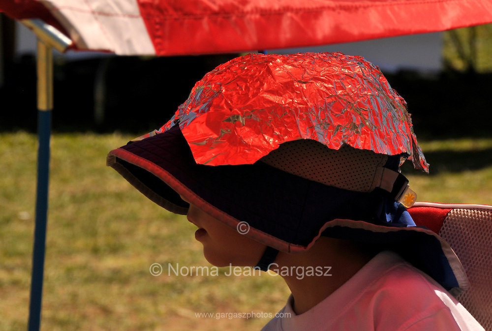 A young boy added recycled aluminum foil to his hat for protection from the sun at the Earth Day celebration at Reid Park, Tucson, Arizona, USA.