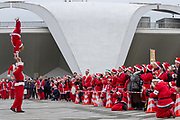 Performers entertain participants before taking part in the Tokyo Great Santa Run in Komazawa-daigaku Olympic Park, Tokyo, Japan. Sunday December 22nd 2019, The great Santa Run was first run in Tokyo in 2018. This years run saw over 3,000 people in Santa costumes run and walk a 4.3 kilometre course to raise money for medical charities in japan and water projects for the Maasai in Kenya.