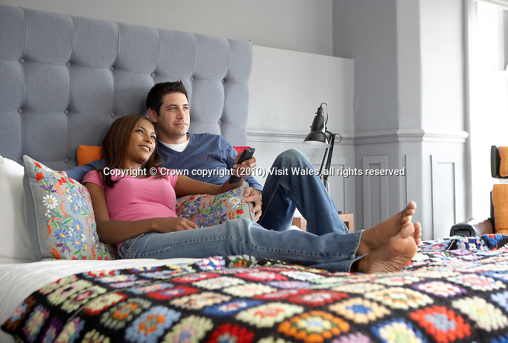 Young adult couple (man and woman) cuddling and relaxing on bed<br /> Bedroom interior<br /> The Escape Hotel<br /> Llandudno<br /> Conwy<br /> North<br /> Bed and Breakfast<br /> Hotels and Accommodation