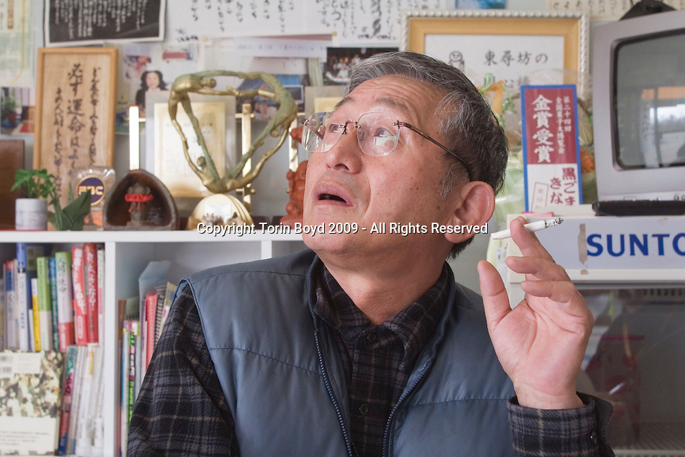 Yukio Shige at his cafe and NPO office at Tojinbo:..This is 65 year old Yukio Shige (pronounced shee-gay), a retired policeman from Fukui Prefecture who founded the NPO suicide prevention group Kokoro ni Hibiku Bunshu Henshukyoku, in order to prevent suicides along the rocky cliffs at Tojinbo. This scenic tourist spot located on the Japan Sea coast in Sakai City, Fukui Prefecture has become a popular suicide spot, with twenty suicides occurring here in 2008 according to city officials. Shige took up his cause in 2004, just before retirement as a police deputy at a nearby police station where he was posted. When he discovered how many suicides were occurring here, he began patrolling the cliffs of Tojinbo in order to spot those contemplating suicide. Shige soon began easily spotting distressed individuals and would talk to them out of their attempts to end their lives. Upon retirement he opened a small cafe at Tojinbo where he also set up his NPO. Since then other volunteers have joined his cause and as of November 2009, Shige explains that he and his group have talked 222 out of committing suicide. They do this by patrolling the cliffs daily with binoculars in hand, and when they spot someone they kindly approach them and coax them away to Shige's cafe where they offer them tea and rice cakes. He also sees them safely home, and in cases where an individual is homeless, he finds them accommodations. However there are still some that slip past his watchful eyes as so far in 2009 thirteen people have jumped to their deaths here. Japan has one of the highest suicide rates in the world and 2009 may surpass the record 34,427 deaths that occurred here in 2003. This increase is thought to be a result of the Japanese recession which has been worsened by the global economic downturn. Depression is the number one cause for suicide in Japan, followed by illness and debt. Photo taken November 27, 2009.