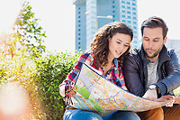 Portrait of young attractive couple sitting while looking in to the map in the middle of the city