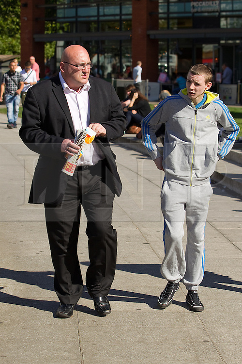 © Licensed to London News Pictures .  08/09/2012 . Manchester, UK . Domenyk Noonan (left) , recently released from prison , walks through Manchester 's Piccadilly Gardens , accompanied by his Nephew , Kieran Noonan (right) . The area was the scene of looting and rioting on 9th August 2011 , during which Noonan was arrested . Noonan has announced he plans to sue the police over the  arrest . Under the terms of a previous early release , the arrest lead to him being recalled to prison . Photo credit : Joel Goodman/LNP