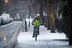 © Licensed to London News Pictures. 01/02/2019. London, UK. A woman cycles through ice and snow in Little Venice in West London as large parts of the UK are deluged with snow and freeing temperatures. Photo credit: Ben Cawthra/LNP