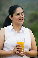 Mid-adult woman holding a glass of orange juice