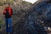 Gabrielle Pétron, a climate scientist from the University of Colorado Boulder, working in NOAA's Earth System Research Laboratory, takes a moment to point out exposed shale outcroppings at Carbon Junction, Durango, Colorado. These outcroppings are a known source of methane emissions in the Four Corners region.