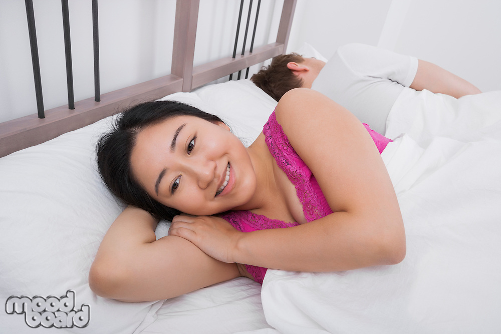 Thoughtful woman smiling while man sleeping in bed