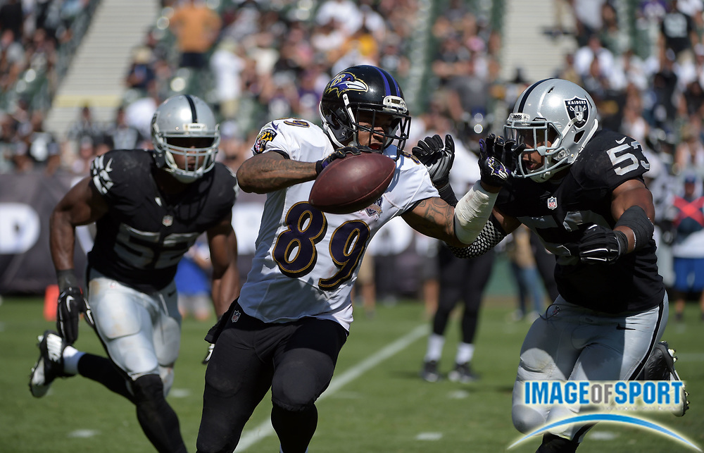 Sep 20, 2015; Oakland, CA, USA; Baltimore Ravens receiver Steve Smith (89) is defended by Oakland Raiders linebackers Khalil Mack (52) and Malcolm Smith (53) in the third quarter at O.co Coliseum. The Raiders defeated the Ravens 37-33.