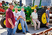 "06 AUGUST 2020 - FAIRFIELD, IOWA: People lean against a John Deere 4020 tractor and watch the bidding during the auction on the Adam Farm near Fairfield. Gary Adam, 72 years old, has been farming in the Fairfield area since 1971. He decided to retire this year because he wants to travel and because it's so difficult to make money in farming this year. He said he wants to ""shed the risk and responsibility. If things were super good, like they were 2006-2012, I might stay in it, but they're not."" Adam did not sell the tractor because it was the first tractor he bought when he started farming. The 4020 tractor was produced from 1964 to 1972. An increasing number of farmers in the Midwest are retiring this year as it becomes harder to make money on crops. In addition to low prices, Iowa farmers are being hit with a drought this year, with well below average rain over most of the state. Because of the COVID-19 pandemic, the auction on Adam's farm was one of the first live in person auctions since winter. Most auctions are now done on line.   PHOTO BY JACK KURTZ"